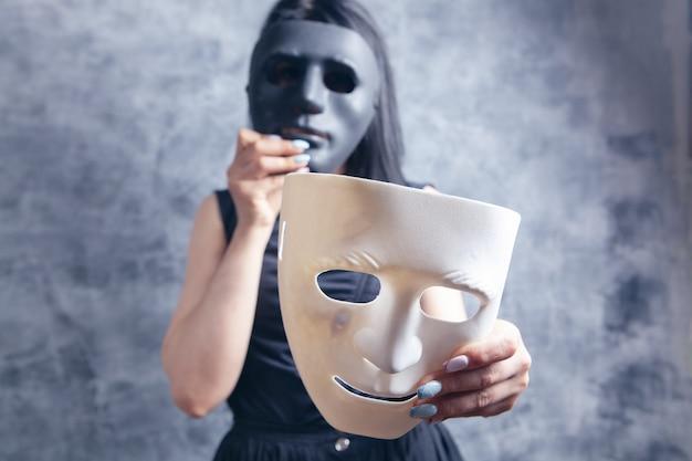 Frau probiert weiße und schwarze plastikmaske an