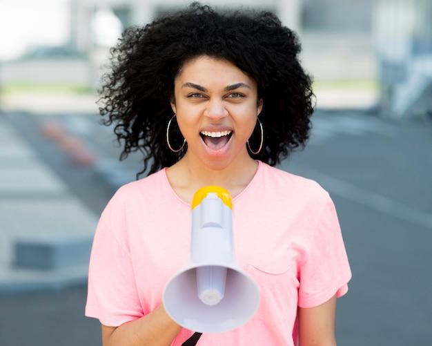 Frau protestiert und schreit im megaphon