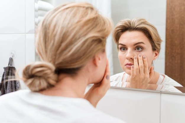 Frau prüft ihre augen im spiegel