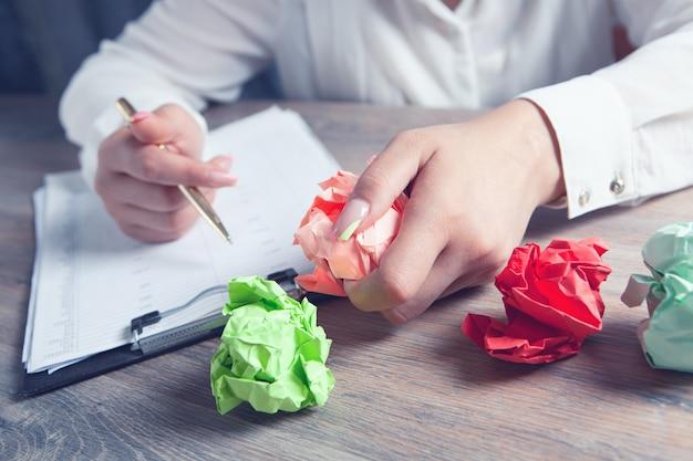 Frau prüft papiere und hält zerknülltes papier