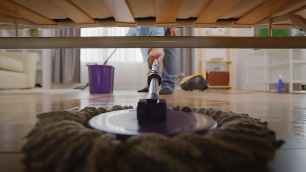 Frau putzt den boden unter dem sofa