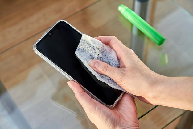 Frau putzt ein smartphone mit einem strahl alkohol aerosol händedesinfektionsmittel und einweg-tuch zu hause. vorsichtsmaßnahmen bezüglich viren