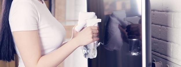 Frau putzt fernseher mit reiniger zu hause