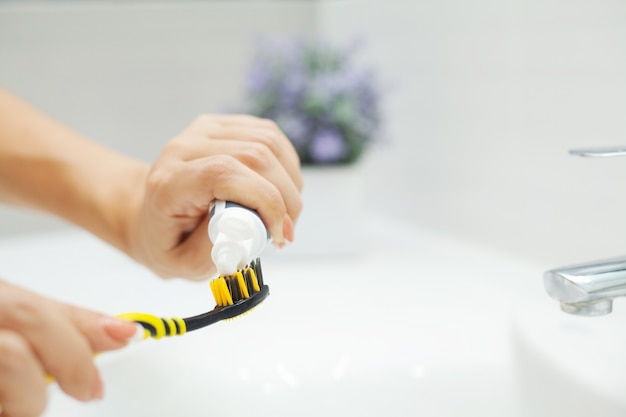 Frau putzt ihre zähne in einem hellen badezimmer
