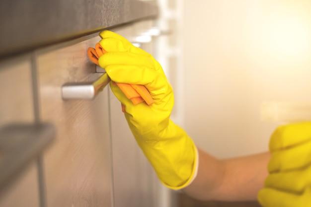 Frau putzt mit einem sprühreiniger zu hause küchenschrank nahaufnahme foto