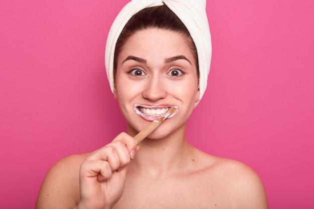 Frau putzt sich die zähne, hat einen erstaunlichen gesichtsausdruck, posiert mit weißem handtuch auf dem kopf und steht mit weit geöffneten augen