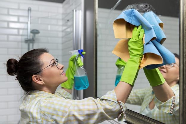 Frau putzt spiegel im badezimmer mit professionellem lappen und waschspray, nahaufnahme
