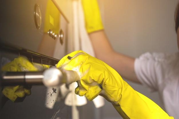Frau putzt und wischt die ofentür-nahaufnahme, um sie in gelben gummihandschuh zu übergeben, hintergrundfoto für das hauswirtschaftskonzept