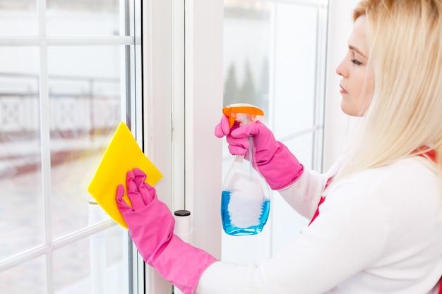 Frau putzt zu hause fenster mit waschmittelreiniger