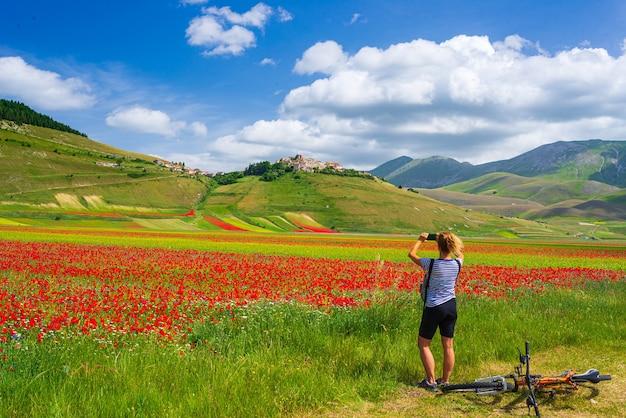 Frau radfahren mtb in blühenden feldern von castelluccio di norcia hochland, berühmte farbenfrohe blühende ebene im apennin, italien. landwirtschaft von entil-getreide und rotem mohn.
