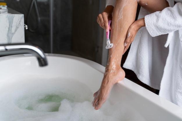 Frau rasiert ihre verzögerung, bevor sie ein bad nimmt