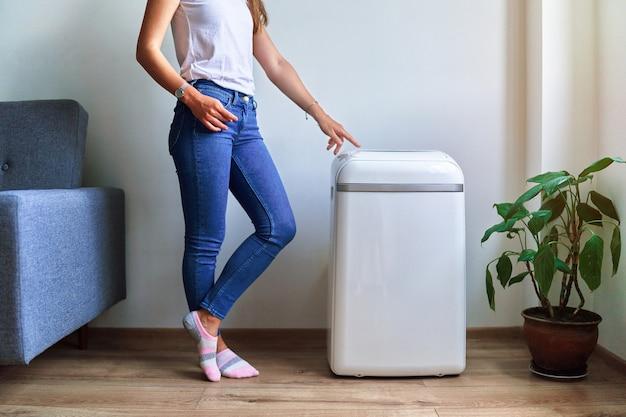 Frau reguliert die kühltemperatur der klimaanlage bei heißem sommerwetter. frische und saubere luft zu hause
