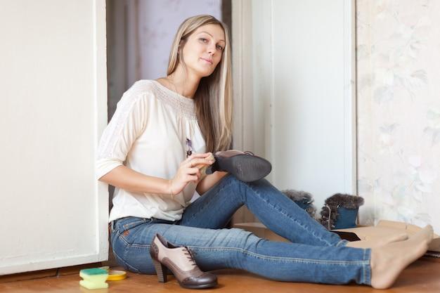 Frau reinigt schuhe