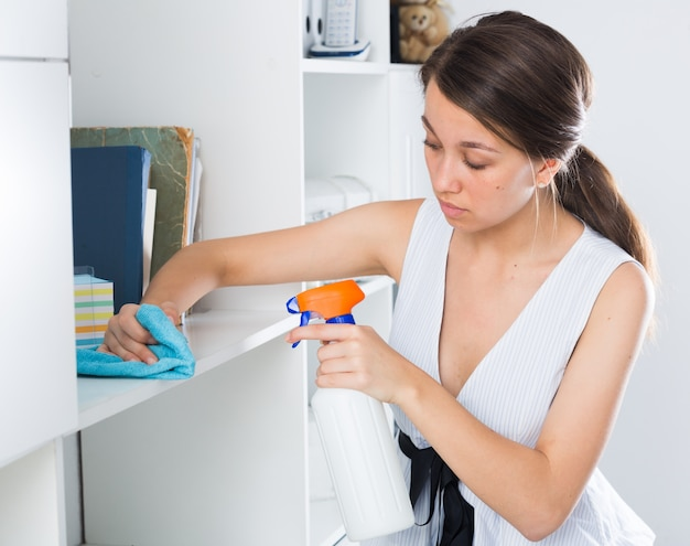 Frau reinigt staub aus regalen