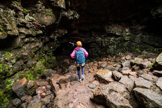 Frau reisende erkunden lavatunnel in island.