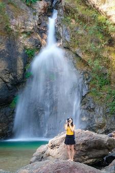 Frau reisende nehmen foto wasserfall von ihrer kamera