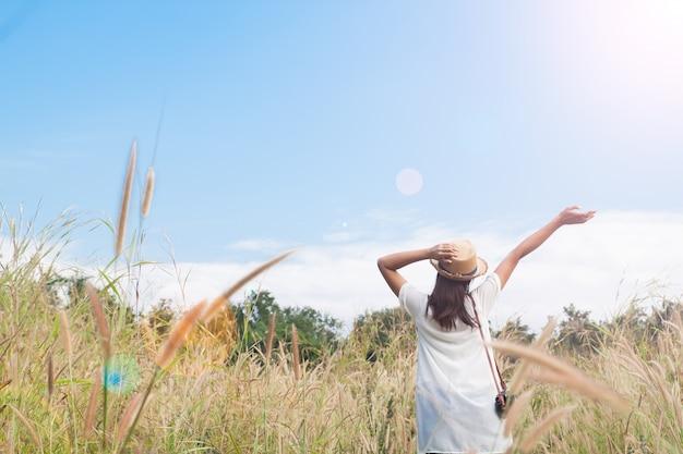 Frau reisender mit kamera holding hut und atmung auf feld von gräsern und wald, wanderlust reise-konzept, platz für text, atmosperic epischen moment