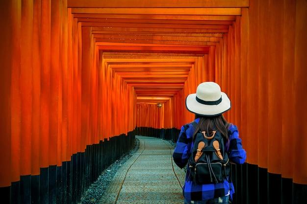 Frau reisender mit rucksack am fushimi inari taisha schrein in kyoto, japan.