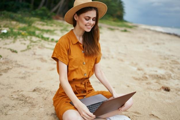 Frau reist mit einem laptop entlang des ozeans entlang des sandes mit palmen