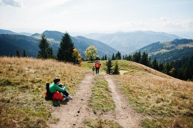 Frau reist mit kindern. mama in den bergen. klettern sie mit kindern auf den gipfel des berges. mit dem rucksack nach oben geklettert.