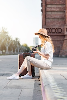 Frau reist und sitzt in der straße von barcelona mit einem koffer und einer vintage-filmkamera.
