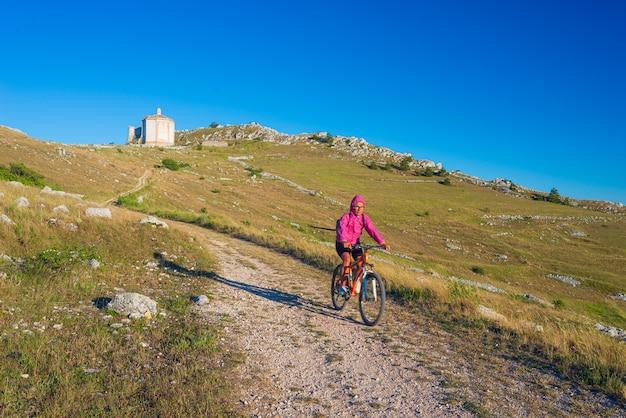 Frau reiten mtb zu burgruine auf berggipfel bei rocca calascio, italienisches reiseziel, nationalpark gran sasso, abruzzen, italien. klarer blauer himmel