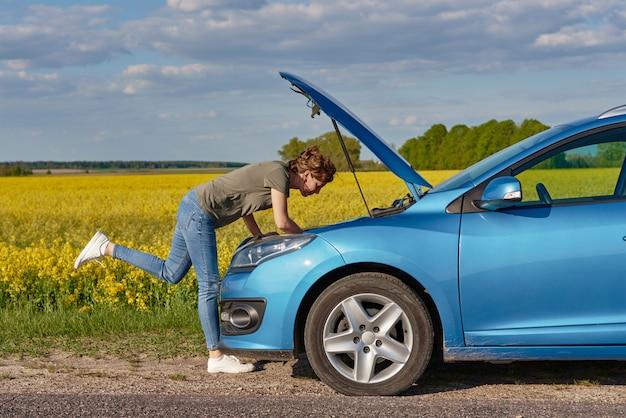 Frau repariert kaputtes auto mit offener motorhaube auf der straße am sommertag