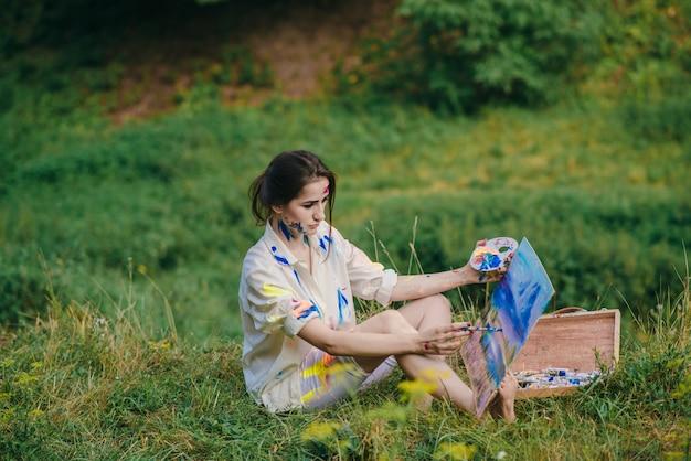Frau retusche ein bild auf dem gras sitzt