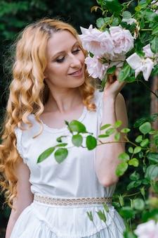 Frau riecht und genießt schöne rosen