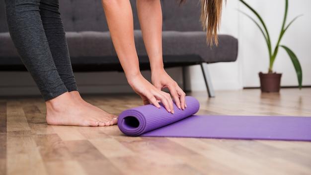 Frau rollende yogamatte