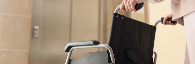 Frau rollt rollstuhl zum aufzug, um behinderte person zu treffen