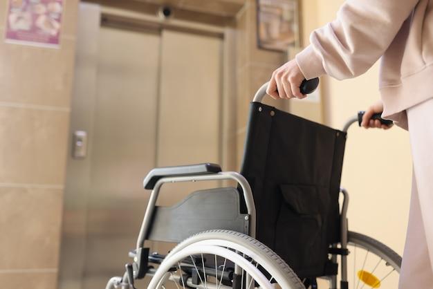 Frau rollt rollstuhl zum aufzug, um eine behinderte person zu treffen