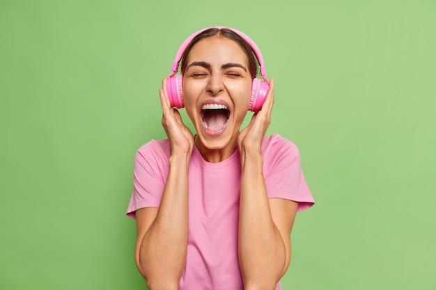 Frau ruft laut aus, hält den mund weit geöffnet hört musik mit lautem ton in kopfhörern trägt ein lässiges t-shirt allein auf grüner schüttelfrost
