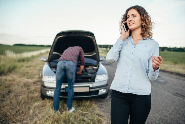 Frau ruft zum service, mann repariert kaputtes auto