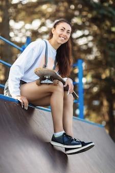 Frau ruht mit einem skateboard in ihren händen vor dem skaten