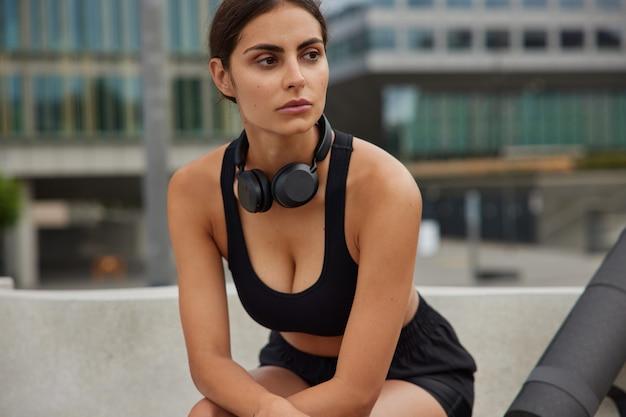 Frau ruht sich nach dem training aus trägt sportkleidung hat regelmäßige joggingübungen im freien gegen die stadtansicht macht pause