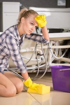 Frau säubert den boden mit eimer wasser.