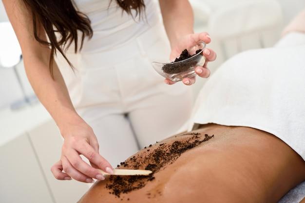 Frau säubert haut des körpers mit kaffeepeeling in der badekurort wellnessmitte.