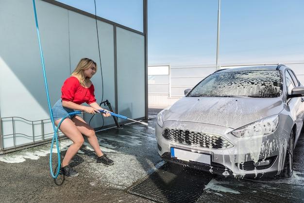 Frau säubert ihr auto mit schlauch mit sprühschaum und manueller autowäsche mit druckwasser von schmutz