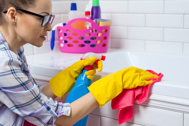 Frau säubert im badezimmer zu hause