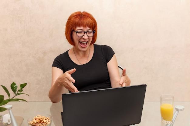 Frau sagt hallo per videochat.