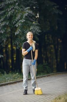Frau sammelt blätter und säubert den park