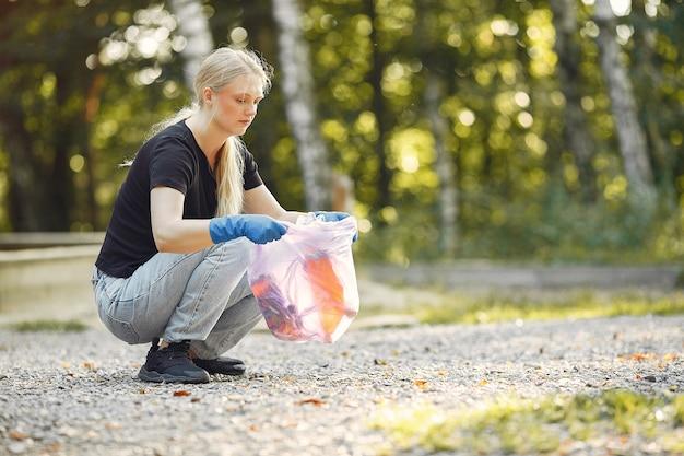 Frau sammelt müll in müllsäcken im park
