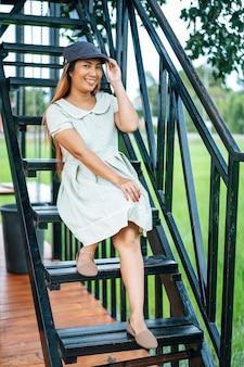 Frau saß glücklich auf der treppe und der griff am hut
