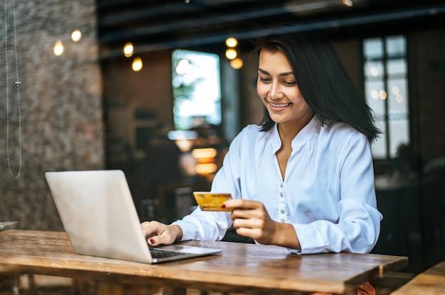 Frau saß mit einem laptop und bezahlte mit einer kreditkarte in einem café