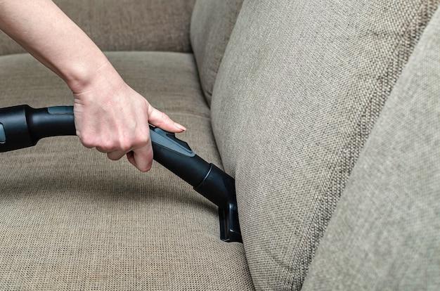 Frau saugt das graue sofa mit einem waschsauger ab. reinigungs- und sauberkeitskonzept.
