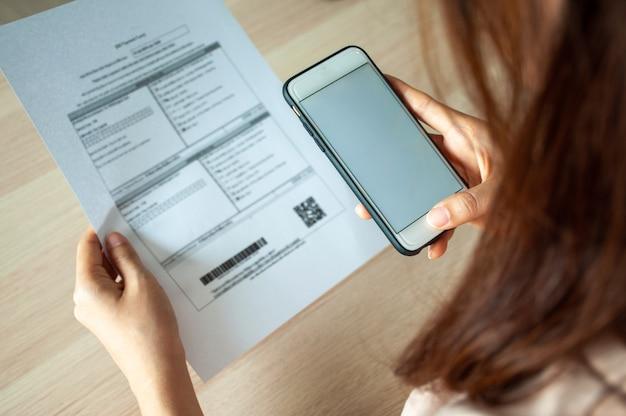 Frau scannt den barcode mit einem smartphone, um monatliche telefonrechnungen zu bezahlen, nachdem sie eine rechnung nach hause geschickt hat