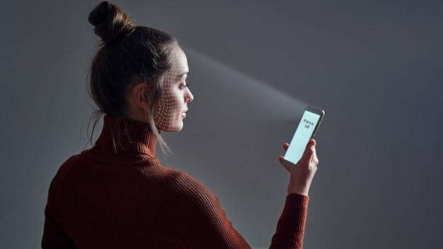Frau scannt gesicht unter verwendung des gesichtserkennungssystems auf smartphone zur biometrischen identifizierung. zukünftige high-tech-technologie und gesichtsausweis