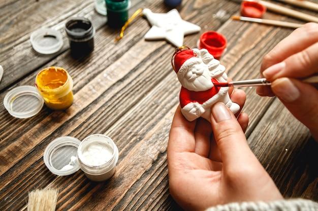 Frau schaffen stilvolle weihnachtsgeschenke, malt porzellanfiguren.