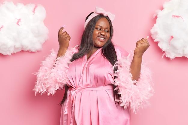 Frau schaut auf ihre neue maniküre kümmert sich um schönheit und aussehen hat langes dunkles haar, das in hausrobe isoliert auf rosa gekleidet ist